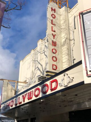 The exterior of a theatre building with a red-lettered sign on a white background reading 'Hollywood'.