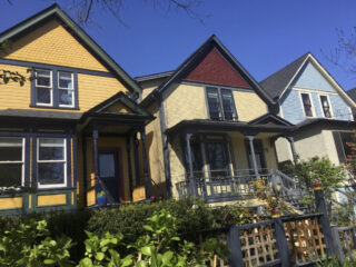 Three heritage homes painted in historically appropriate colours.