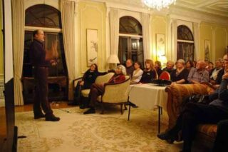 A man presents in front of an audience inside a heritage building.