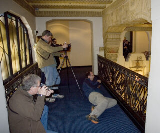 Several people taking photographs of the interior of an Art Decor heritage building.
