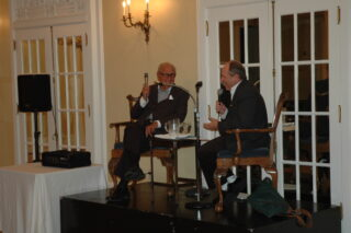 Two men sit in chairs holding microphones, talking.