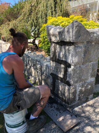 A mason sitting on a bucket, repointing a stone pillar